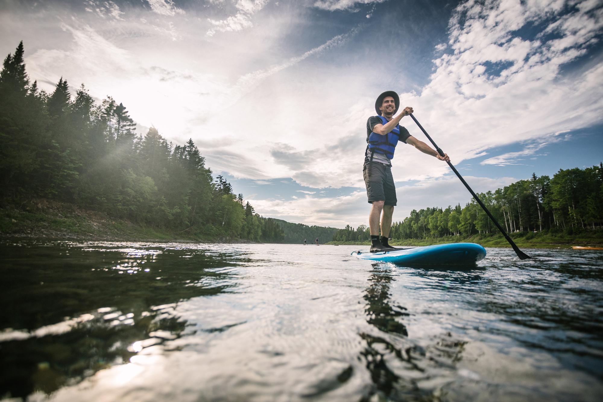 Un homme descend la rivière Bonaventure en planche à pagaie