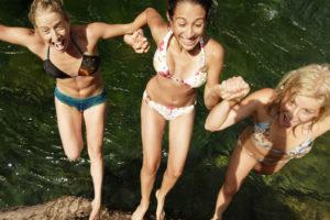 3 femmes qui sautent d'une roche au Malin